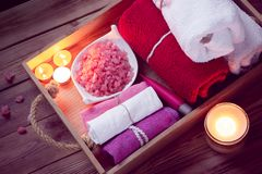 Set of bathhouse accessories for SPA in Low-key lighting. SPA consist from colorful towels, pink sea salt and candles on a wooden tray. Picture in Low-key stock images