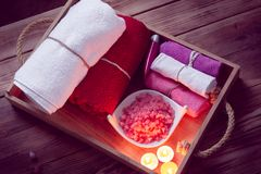 Set of bathhouse accessories for SPA in Low-key lighting. SPA consist from colorful towels, pink sea salt and candles on a wooden tray. Picture in Low-key royalty free stock images