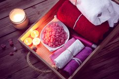 Set of bathhouse accessories for SPA in Low-key lighting. SPA consist from colorful towels, pink sea salt and candles on a wooden tray. Picture in Low-key stock photos