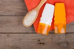 Set of bathing accessories - orange towel, hairbrush and cosmetics for pampering on brown wooden background royalty free stock images