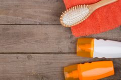 Set of bathing accessories - orange towel, hairbrush and cosmetics for pampering on brown wooden background stock photo