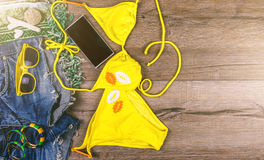 Set of beach clothes yellow bikini, bracelets, jeans shorts, glasses on dark wooden background. Top view. Summer Holiday Stock Image