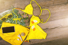 Set of beach clothes yellow bikini, bracelets, shorts, glasses on dark wooden background. Top view. Summer Holiday Stock Image