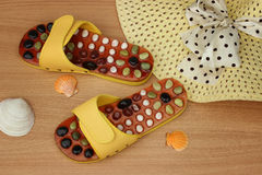 Set for the beach: yellow flip-flops and a straw hat with a bow and seashells close-up on a wooden background Stock Photos