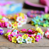 Set of beautiful bracelets on vintage wooden background. Bracelets made of colorful plastic flowers, leaves and beads Royalty Free Stock Photos