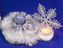Set beautiful glass poured New Year`s balls, brilliant tinsel, the burning candle and a snowflake on a blue background - New Year`. S composition, a card Stock Photo