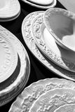 Set of beautiful white ceramic dinner relief plates on black background Stock Images