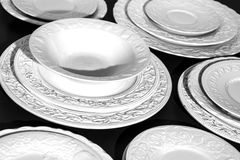 Set of beautiful white ceramic dinner relief plates on black background Stock Photo