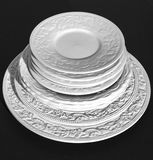 Set of beautiful white ceramic dinner relief plates on black background Royalty Free Stock Image