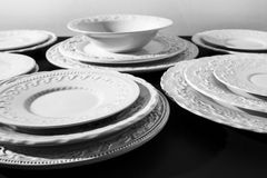 Set of beautiful white ceramic dinner relief plates on black background Royalty Free Stock Photography