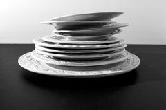 Set of beautiful white ceramic dinner relief plates on black background Stock Photography