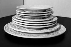 Set of beautiful white ceramic dinner relief plates on black background Royalty Free Stock Images