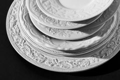 Set of beautiful white ceramic dinner relief plates on black background Stock Photos