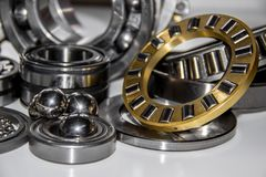 A set of big stainless balls in the middle and on top of ball bearing and a set of various bearings Stock Photo