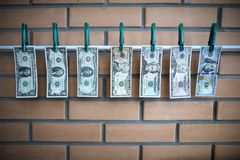 Concept of money laundering - dollars are drying on lath on on brick wall background stock images