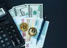 Set of bitcoin, crypto currency with yellow paper arrows next to notepad on real money background. Time is money. Internet e-commerce, security, risk royalty free stock image