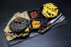 Set of the black burger. Stone plate with: black burger roll slices of juicy marble beef, fused cheese, fresh salad with French fr Stock Photos