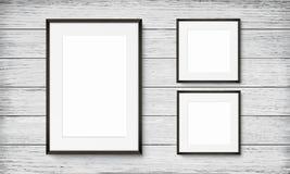Set of black frames on wooden background Stock Images