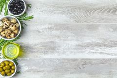 Set of black and green olives, quail eggs on plates, olive oil a. Nd rosemary, on a light gray wooden background. Top view, copy space stock photo