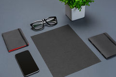 A set of black office accessories, glasses, green flower and smart on gray background Stock Photos
