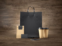 Set of black shopping bag, craft package, two brown coffee cups, blank business cards and generic design smartphone Stock Photos