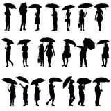 Set of black silhouettes of men and women with. Umbrellas. Vector illustration Royalty Free Stock Photography