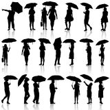 Set of black silhouettes of men and women with. Umbrellas. Vector illustration Royalty Free Stock Image