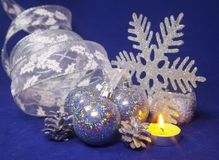 Set blue beautiful glass New Year`s balls, brilliant tinsel, the burning candle on a blue background - New Year`s composition,. Set blue beautiful glass New Year Stock Images