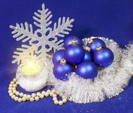 Set blue beautiful glass New Year`s balls, brilliant tinsel, the burning candle and a pearl beads on a blue background - New Year. `s composition, a card Stock Image