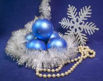 Set blue beautiful glass New Year`s balls, brilliant tinsel,  and a pearl beads on a blue background - New Year`s composition, a c. Ard Stock Image