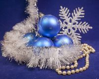 Set blue beautiful glass New Year`s balls, brilliant tinsel,  and a pearl beads on a blue background - New Year`s composition, a c. Ard Royalty Free Stock Photos