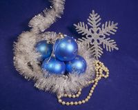 Set blue beautiful glass New Year`s balls, brilliant tinsel,  and a pearl beads on a blue background - New Year`s composition, a c. Set blue beautiful glass New Royalty Free Stock Photo
