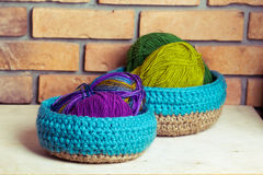 Set of blue knitted baskets. Set of knitted baskets on brick background Royalty Free Stock Image