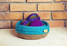 Set of blue knitted baskets. Set of knitted baskets on brick background Royalty Free Stock Photography