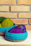 Set of blue knitted baskets. Set of knitted baskets on brick background Royalty Free Stock Photo