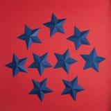 Set of blue paper stars. On red background royalty free illustration
