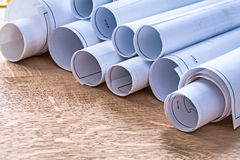 Set of blueprint rolls on wooden oaken board Royalty Free Stock Images