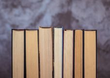 Set of books ordered. Set of ordered books in which you can see the used sheets that symbolize their regular reading. Image on an abstract background Royalty Free Stock Image
