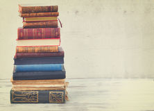 Set of books. Tower of books on white wooden desktop, retro toned royalty free stock photography
