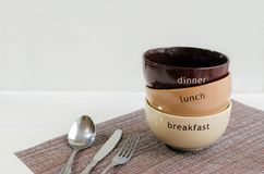 Set of bowls. Written breakfast, lunch, dinner. On ceramic bowls. Menu concept stock image