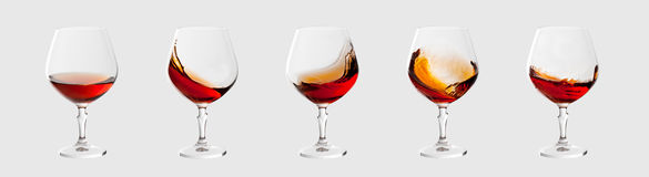 Set of brandy glasses with splashes isolated on light grey Stock Image