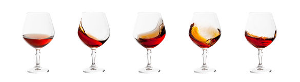 Set of brandy glasses with splashes isolated on white Stock Images