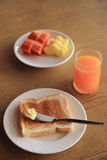 Set of breakfast, plate of toast with butter and fresh fruit and orange juice Stock Photography