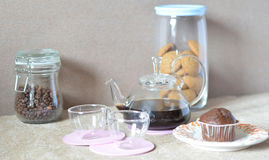 A set breakfast table. Round glass kettle wiht coffee, two cups, muffin, sugar, a can of coffee Royalty Free Stock Photos