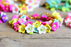Set of bright bracelets on old wooden background. Bracelets made of colorful plastic flowers, leaves and beads. Accessories Stock Image
