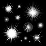 Set of bright glowing light stars burst on black background. Glitter suns effect decoration with ray sparkles for your design. Abstract night sky objects Stock Image