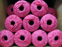 Set of bright pink rayon chenille yarn balls. In a carton box Stock Images