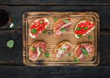 Set of bruschetta served on wooden board with wine Royalty Free Stock Photo
