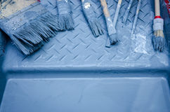 Set of brush and blue paint in paint tray. House renovation tools. Old used brushes and blue paint in paint tray Royalty Free Stock Photography