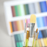 Set of brushes in a can. With colorful background Royalty Free Stock Photography